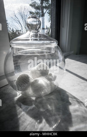 Cotton Balls In Glass Jar By Sunlit Bathroom Window - Stock Image