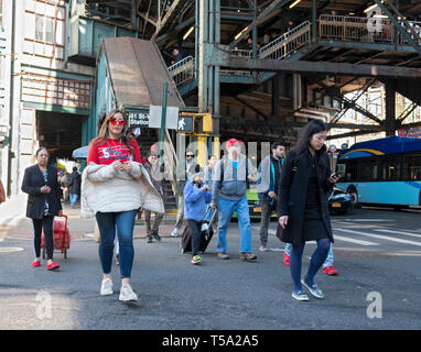 A diverse group of passengers gettin off the elevated #7 train on Roosevelt Avenue in Woodside, Queens, New York. - Stock Image