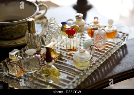 Glass tray filled with vintage perfume bottles on display in antique shop - Stock Image