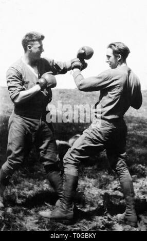 Two young men engage in a boxing match out in a field, ca. 1930. - Stock Image