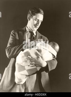 Man holding baby wrapped in a blanket - Stock Image