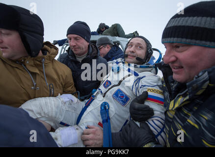 Russian cosmonaut Alexander Misurkin is helped out of the Soyuz MS-06 spacecraft just minutes after he, NASA astronauts Joe Acaba, and Mark Vande Hei, landed in a remote area near the town of Zhezkazgan, Kazakhstan on Wednesday, Feb. 28, 2018 (February 27 Eastern time.)  Acaba, Vande Hei, and Misurkin are returning after 168 days in space where they served as members of the Expedition 53 and 54 crews onboard the International Space Station. - Stock Image