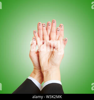 Finger on two hands with face as teamwork concept - Stock Image