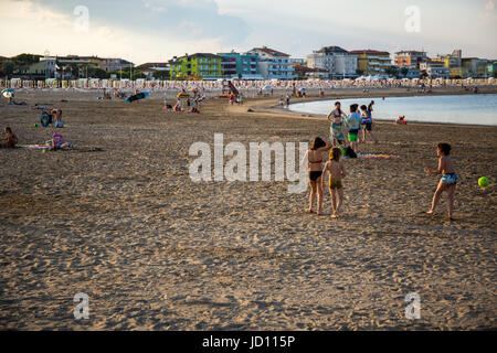 Caorle, Italy. 17 th June 2017. A group of children having fun playing football on the beach at the evening. Credit: - Stock Image