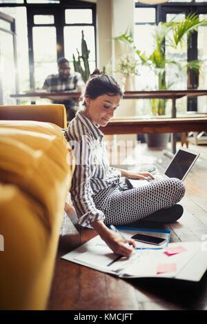 Female freelancer working at laptop, taking notes on living room floor - Stock Image