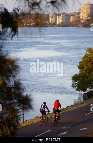 Cycling along Coronation Drive Brisbane queensland Australia - Stock Image