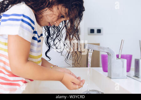 little girl taking water to wash her face in the bathroom at morning after shower, kids hygiene concept - Stock Image