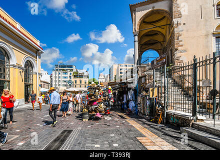 Tourists shop and sightsee the stores, marketplace and stalls selling gifts in the Monastiraki Square on a sunny day in Athens, Greece. - Stock Image
