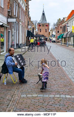 A young girl gives a coin to a street musician playing his accordion on Jufferenstraat in the old Hanseatic town of Elburg, Netherlands. - Stock Image