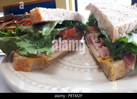 Delicious looking ham and cheese sandwich on a restaurant plate - Stock Image