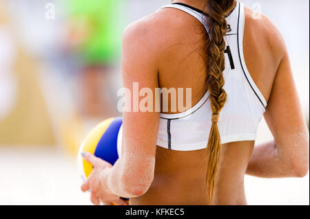 Volleyball beach player serving is a female beach volleyball player getting ready to serve the ball. - Stock Image