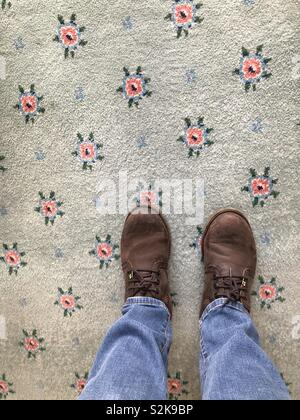 POV boots on a flowery carpet - Stock Image