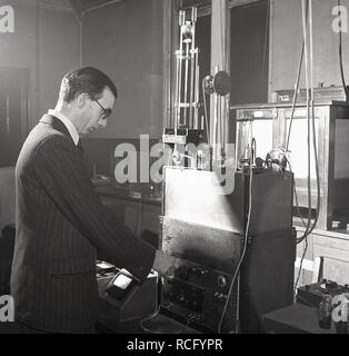 1950s, historical, Leeds University, Science laboratory, male scientist using testing equipement - Stock Image