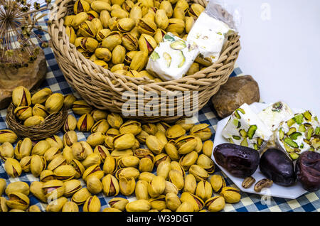 Oriental dessert of pistachios, persimmons and nougat in a wicker basket and on a white plate next to the stones and dried flowers on paper with blue - Stock Image