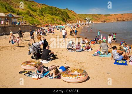 UK, England, Yorkshire, Filey, visitors on beach near Coble Landing - Stock Image