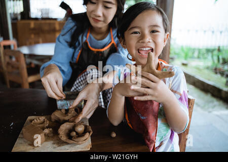 Pottery workshop. A potter craftwoman shows his child how to work with clay - Stock Image
