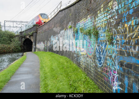 Graffiti covered canalised wall and rail line - Stock Image