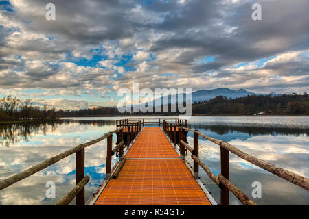 pier on the lake of Varese with cloudy sky at the autumn sunset - Stock Image