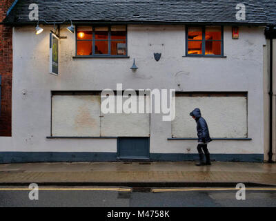 Ashbourne, UK. 14th Febraury, 2018. Woman walking past the Artisan Bar at the end of the wet two day Ashbourne Royal - Stock Image