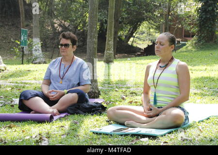 Two women meditating in outdoors on a lawn at a yoga retreat in India - Stock Image