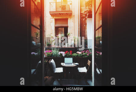 Small cozy beautiful workspace on balcony with laptop, mouse, smartphone, two chairs and flowers around on sunny - Stock Image