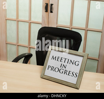 meeting in progress sign in front of closed doors - Stock Image