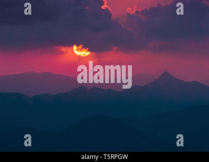 dark background with sun and clouds over far mountains at sunset - Stock Image