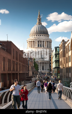 tourists walking along the millenium bridge with st pauls cathedral behind - Stock Image