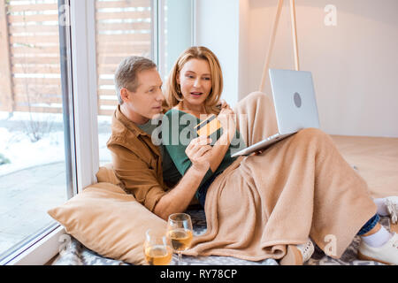 husband holding credit card while using laptop with wife - Stock Image