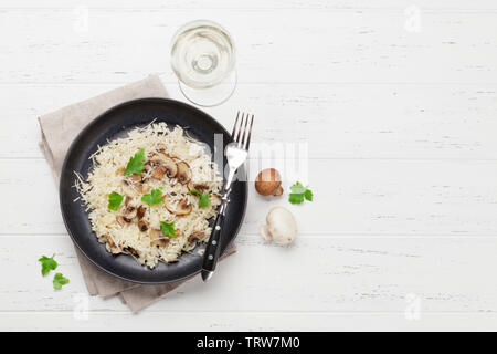 Delicious mushrooms risotto dressed with parmesan cheese and parsley. With white wine glass. Top view with copy space - Stock Image