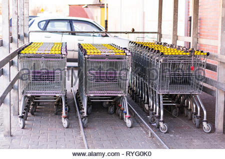 Poznan, Poland - February 24, 2019: Three rows of metal locked shopping carts of a German Netto supermarket. - Stock Image