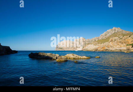 Rocks bathed in late afternoon sunlight in the Mediterranean sea in Cala San Vicente, Mallorca, Spain. - Stock Image