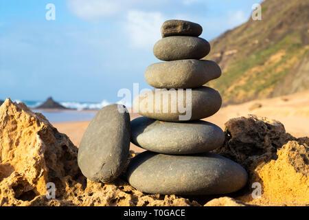 Rock balancing stone stacks on beach cairn Algarve Portugal EU Europe - Stock Image