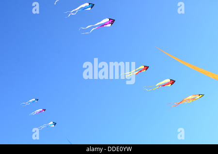 Flying kites in a clear blue sky - Stock Image