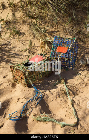 Two old and worn-out, hand made, crab traps washed away by tides and waves into the sand dunes. Iron and colored - Stock Image