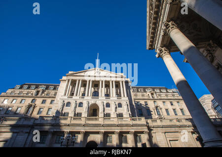 A view of the exterior of The Bank of England - the central bank of the UK, with the Royal Exhange building on the right-handside, in London, UK. - Stock Image