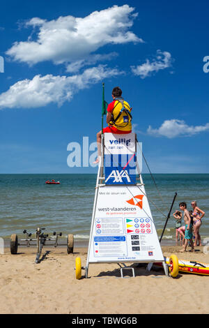 Beach lifeguard supervising bathers and swimmers along the Belgian North Sea coast from portable high chair / tower, Belgium - Stock Image
