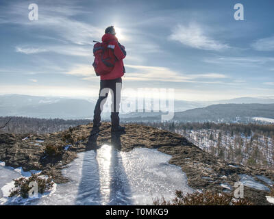 Standing man with raised arm on icy stone and looking on snow covered mountains. Landscape with traveler, - Stock Image