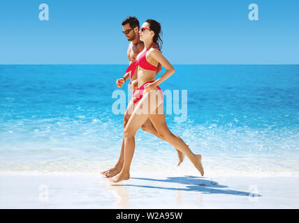 Fit couple doing jogging on a hot, tropical beach - Stock Image