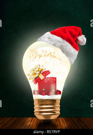 Glowing light bulb wearing Santa hat with Merry Christmas message and magical gift box and baubles with copy space. Glowing Xmas and season of sharing - Stock Image
