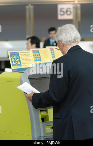 passengers checking-in at British Airways self-service check-in kiosks managed by Aviance in Manchester Airport Terminal3, IBM series N kiosks - Stock Image