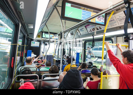 Miami Beach Florida North Beach Miami-Dade Metrobus public bus transportation inside passengers riders onboard standing sitting - Stock Image