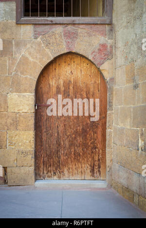 Old wooden door framed by arched bricks stone wall at the courtyard of al Razzaz historic house, Darb al Ahmar district, Old Cairo, Egypt - Stock Image