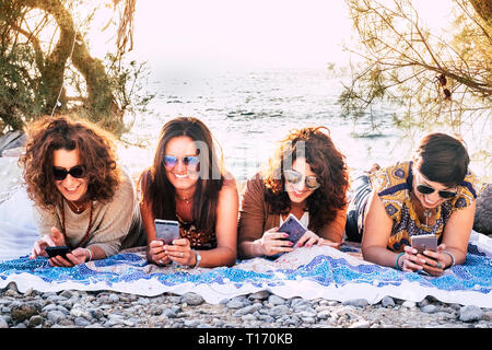 Middle age beautiful women lay down on the rocks with ocean in background for outdoor leisure vacational activity using everybody her own mobile phone - Stock Image