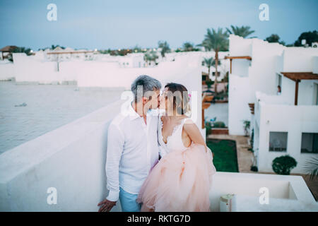 Happy newlyweds kiss on terrace of white house against background of palms during the honeymoon in Egypt. - Stock Image