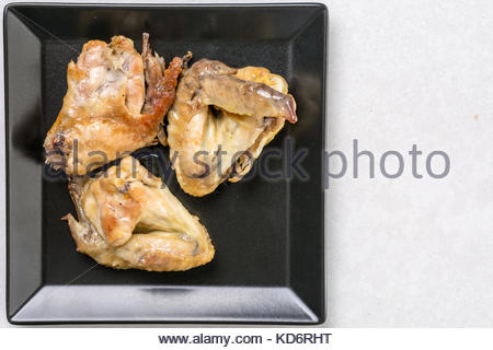 Flat lay above black plate with fried chicken wings on the white marble table. - Stock Image