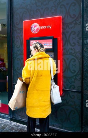 Young woman in a yellow coat with a hand bag and shopping at a Virgin Money ATM cash machine - Stock Image