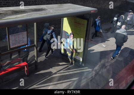 Young pedestrians pass-by a bus stop ad, on 11th March 2019, in London, England. - Stock Image