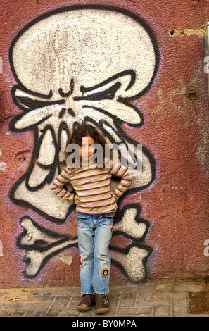 young girl in front of a graffiti wall with painted skull - Stock Image