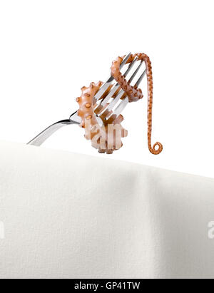 An Octopus tentacle wrapped around and dangling from a silver fork - Stock Image